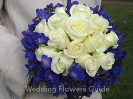 Blue delphinium bridal bouquet featuring white roses