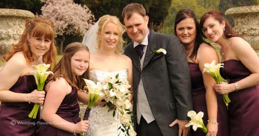 Elegant white wedding flowers held by bride, bridegroom and bridesmaids