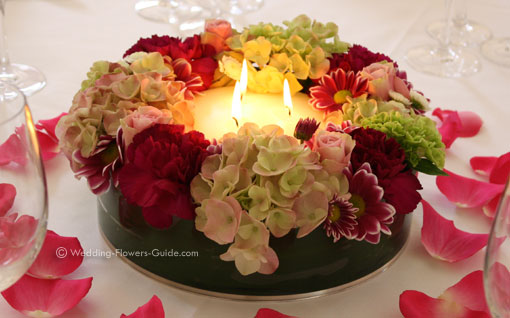 Low candle wedding centerpiece surrounded by flowers