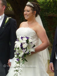 bride holding purple and ivory bridal bouquet