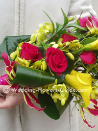tropical sheaf bouquet featuring calla lilies, roses and gloriosa