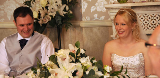 wedding reception flowers with bride and groom