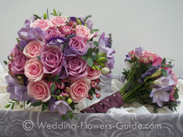 bride and bridesmaids bouquet showing design of handle which is ribboned to match the bridesmaids dress