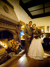country house winter wedding - couple in front of open fire