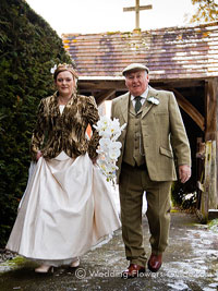 bride and father with wedding flowers, walking to church for a winter wedding